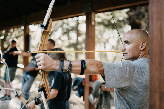 an archer pulls back his bow