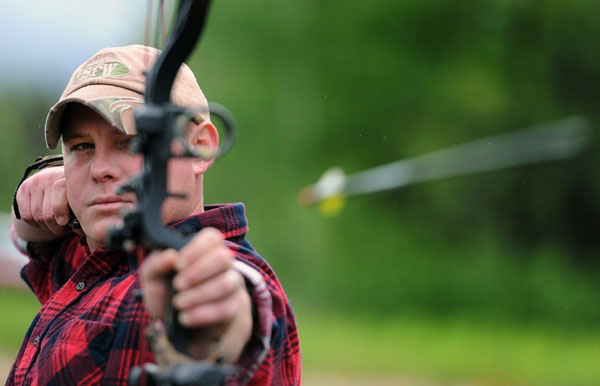a man firing a compound bow with sights
