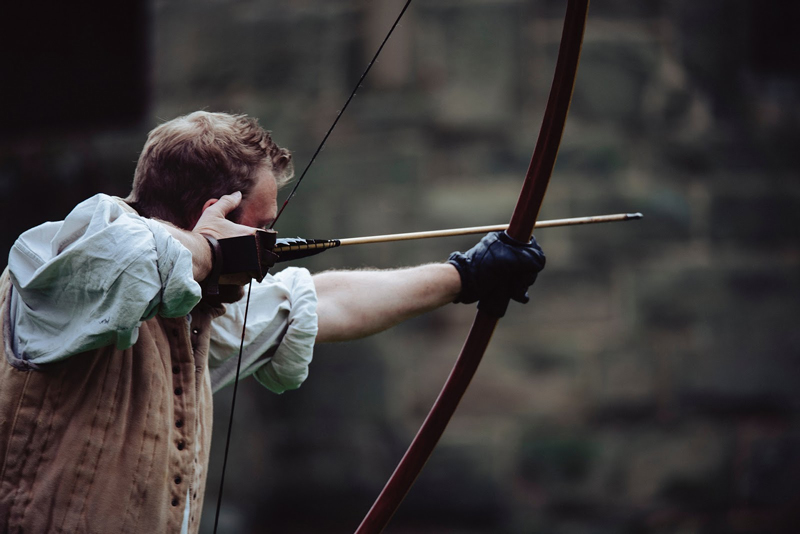 man shooting longbow type of bow