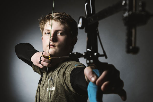 young man using release aids with a compound bow